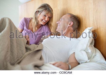 Happy senior couple in bed - Stock Photo