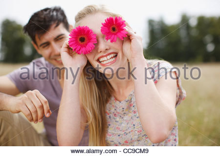 Portrait of playful woman holding flowers over eyes in rural field - Stockfoto