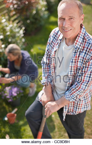Portrait of smiling senior man working in sunny garden - Stock Photo