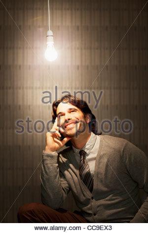 Smiling businessman sitting under illuminated light bulb - Stockfoto