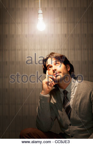 Pensive businessman sitting under illuminated light bulb - Stockfoto