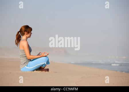 Beautiful young woman on the beach doing yoga exercises - Stock Photo