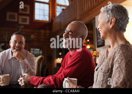 Mature friends laughing together in living room - Stock Photo