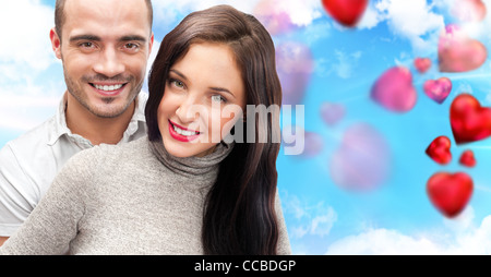 Beautiful young couple embracing and looking at camera. Standing at romantic background, designed in valentine style - Stock Photo