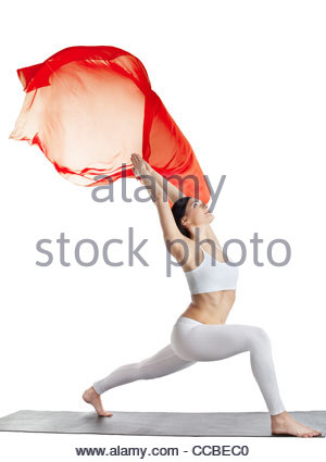 Young beauty woman in yoga uttkatasana and red flying cloth isolated - Stock Photo