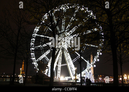 Place de la Concorde, Christmas Ferris wheel by night, and view of the Eiffel Tower, Paris, France - Stock Photo