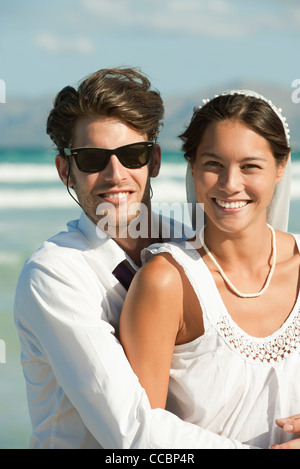Bride and groom at the beach, portrait - Stock Photo