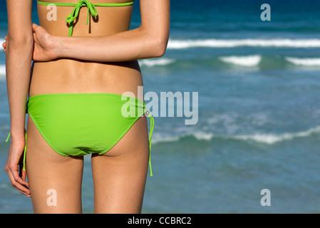 Woman in bikini standing by sea - Stock Photo