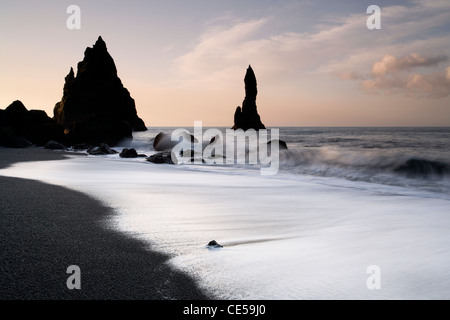Waves washing in around black volcanic sea stacks on the Vik coast in Iceland - Stock Photo