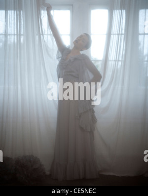 A woman wearing a long grey dress, standing behind a voile curtain - Stock Photo