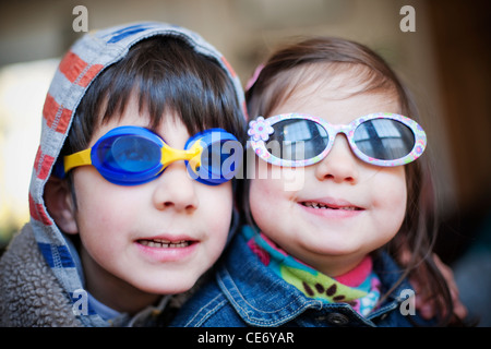 Two children wearing swimming goggles and sunglasses - Stock Photo