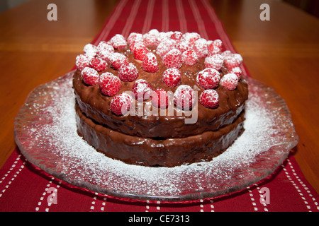 Whole delicious birthday cake with chocolate ganache and raspberries with dusting of powdered sugar. - Stock Photo