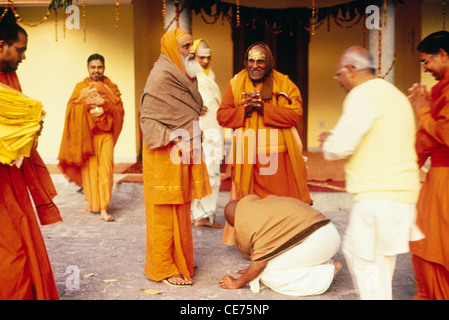 RVA 83089 : hindu man bending to give respect to an indian sanyasi india - Stock Photo