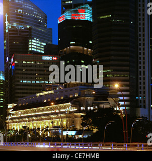 The Central Business District skyline and the Fullerton Hotel at night in Singapore in Asia. - Stock Photo