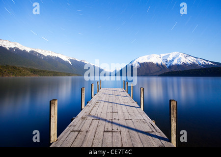The jetty at Lake Rotoiti, Nelson Lakes National Park, New Zealand, by moonlight. Star trails can be see in the - Stock Photo