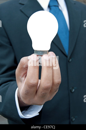 Business man with lit bulb - Stock Photo