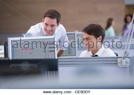Smiling businessmen working at computer in office - Stock Photo
