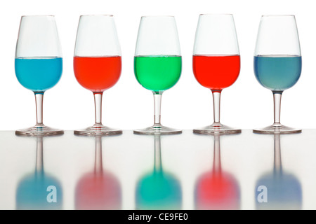 glasses of colored liquid photographed on a white background - Stock Photo