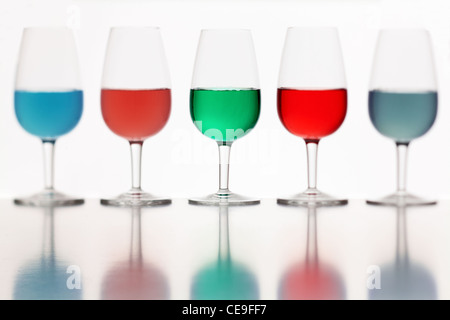 defocused glasses of colored liquid photographed on a white background - Stock Photo