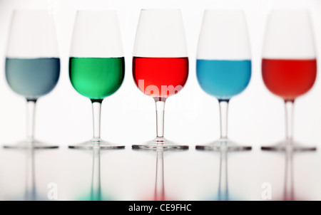 de-focused glasses of colored liquid photographed on a white background - Stock Photo