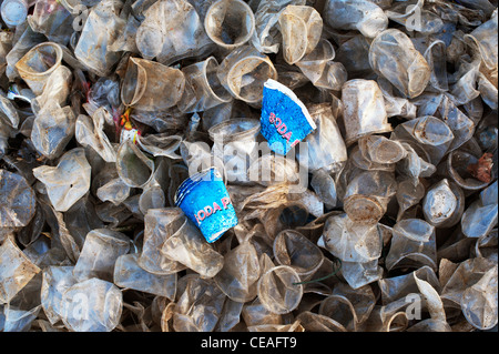 Discarded paper soda cups amongst plastic tea cups in the Indian countryside. Andhra Pradesh, India - Stock Photo