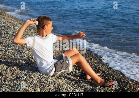 Child Throwing Stones Into The Sea In Portugal Algarve