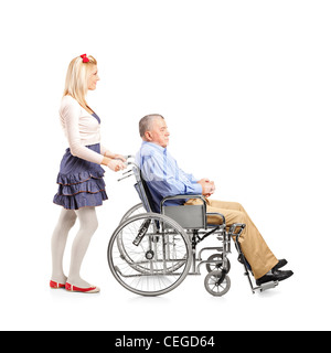 Full length portrait of a daughter pushing her dad in a wheelchair isolated on white background - Stock Photo