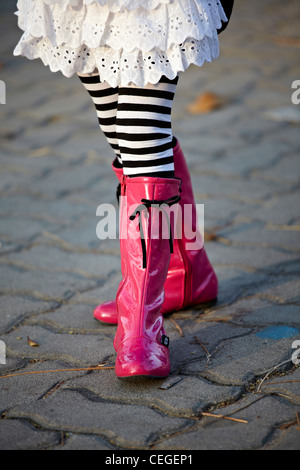 Trendy and fashionable girl in pink boots and striped leggings - Stock Photo