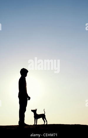 Silhouette of young Indian boy standing with his puppy. India - Stock Photo