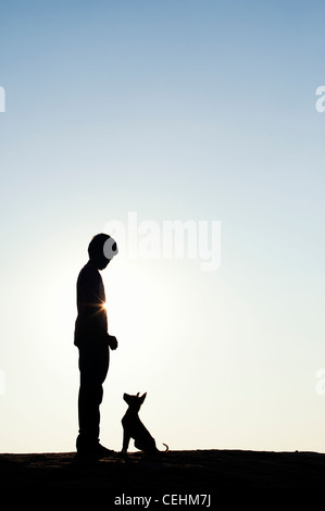 Silhouette of young Indian boy standing with his puppy - Stock Photo