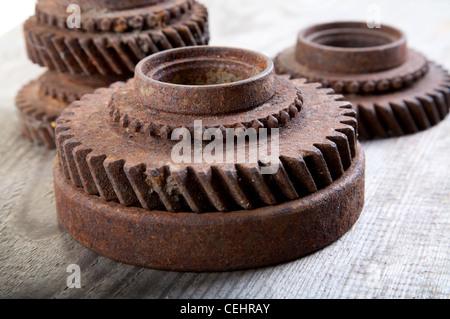 Rusty iron gear wheels on a board - Stock Photo