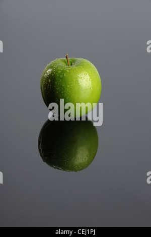 Green apple with reflection on a gray background - Stock Photo