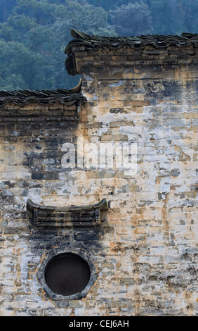 A Chinese hui style residential house, high white textured wall and black roof with tiered design - Stock Photo