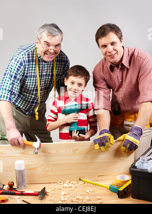 Vertical shot of three multigenerational guys working in a woodshop and smiling at camera - Stock Photo