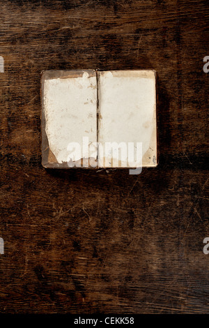 very old book lying open on old wooden table - empty pages - Stock Photo