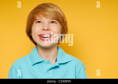 Cute eleven year old boy is smiling and looking up toward the top of the frame. - Stock Photo