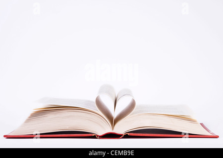 book with heart shaped pages over white background - Stock Photo