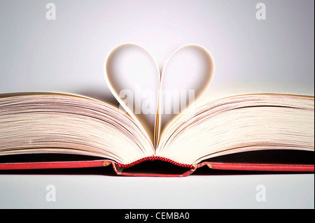 book with heart shaped pages over gradient background - Stock Photo