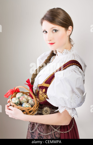 Beauty woman in traditional Polish clothes holding wicker basket with Easter eggs, Cieszyn Silesia region, studio - Stock Photo