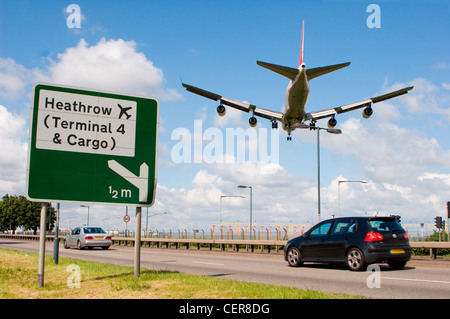 Cars on the A4 passing a road sign for Heathrow airport as a plane comes into land directly overhead. - Stock Photo
