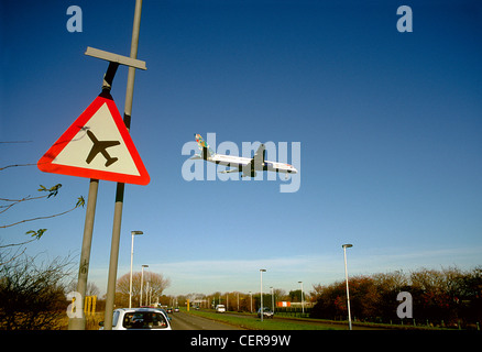 An aircraft coming in to land at Heathrow airport passing above a low flying plane sign by the roadside. - Stock Photo