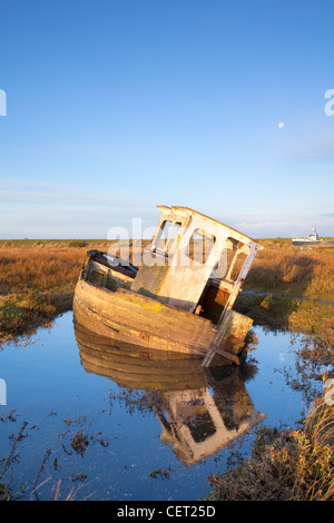 A derelict boat at Thornham Harbour at first light. - Stock Photo