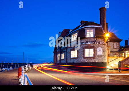 Light trails from cars passing the Blakeney Hotel on the Norfolk Coast at dusk. - Stock Photo