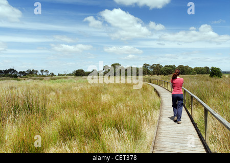 A young woman crossing a grassy field on a wooden boardwalk - Stock Photo