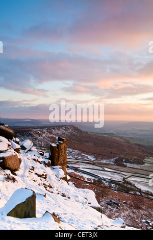 Curbar Edge and the Pinnacle rock illuminated by the last rays of the setting sun in the Peak District National - Stock Photo
