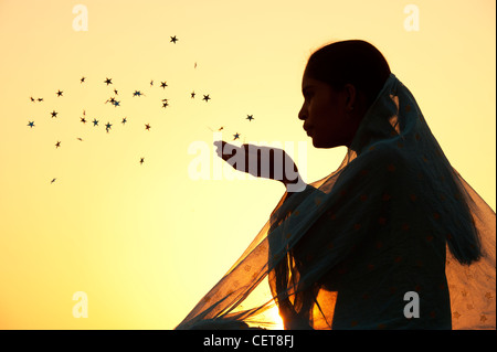Indian girl wearing a star shawl blowing stars into the air. Silhouette - Stock Photo