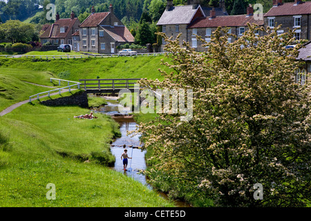 A boy wading in the stream at Hutton Le Hole, picturesque village on the Yorkshire moor. - Stock Photo