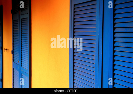 Blue window shutters against a yellow wall at Beverley in East Yorkshire. - Stock Photo