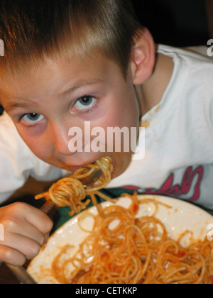 Male child short blond hair wearing white t shirt red letters leaning over white plate of spaghetti tomato sauce - Stock Photo