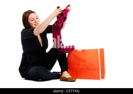 Portrait of an attractive young girl checking her new top from shopping bag on white background  - Stock Photo